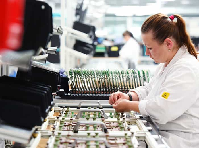 A worker is performing a through-hole PCB assembly job